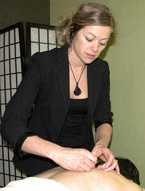 Kelli Irvine NP examines the placement of acupuncture needles in her client's back. Image by Marlene Eisner.