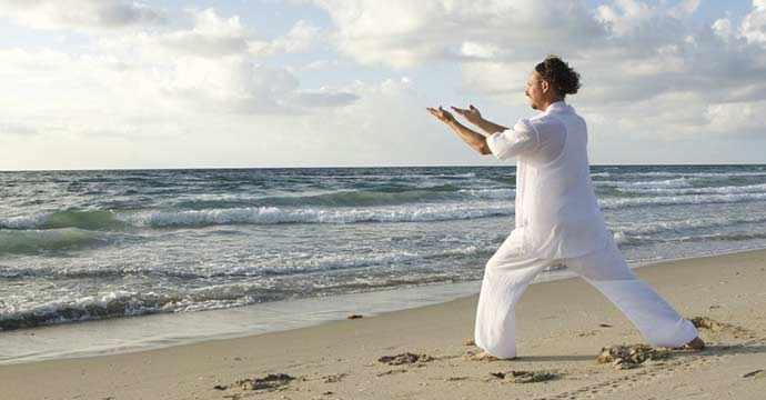 practicing Qi Gong on beach - WestmountMag.ca